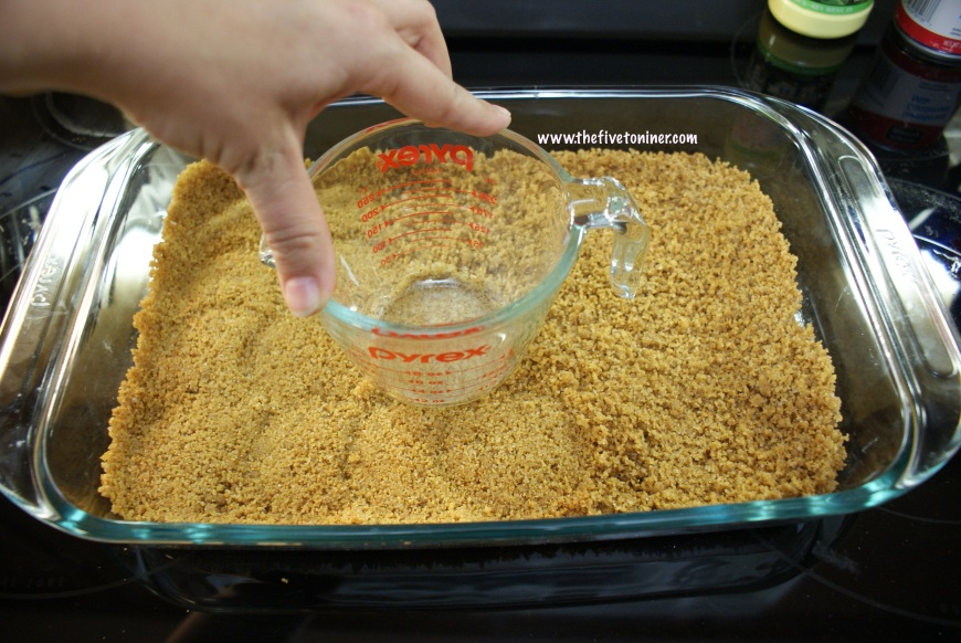 Use a clean flat bottomed object (in this case, a measuring cup) to press the crust mixture into the dish.